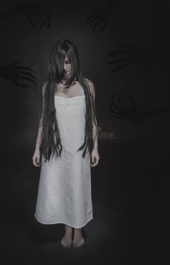 Mystisk spökekvinna med långa svart hår- och skuggahänder på da royaltyfria bilder