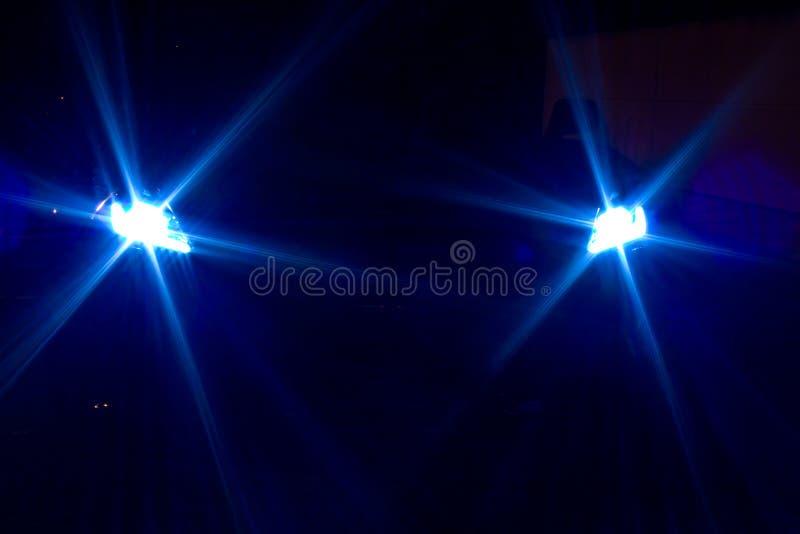 Mystisk sportbil i skuggorna Blåa xenonbillyktor på natten av en sportbil arkivfoton