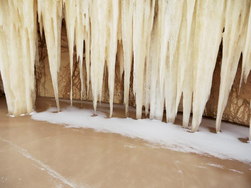 Mystiska jätte- istappar i den sandiga grottan nära den djupfrysta vintersjön arkivfoton