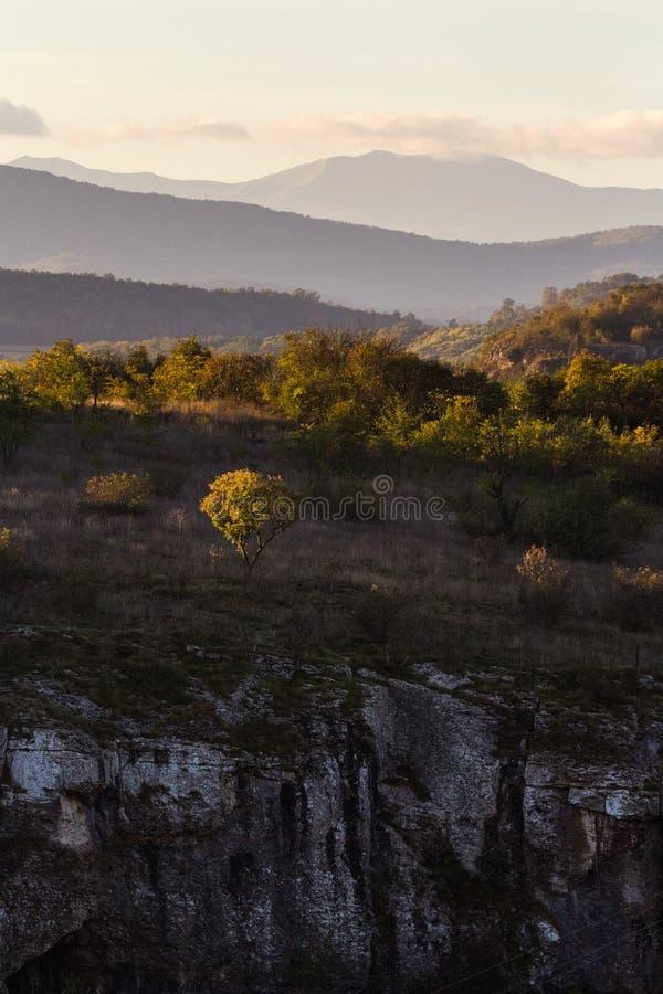 Mystiskt solnedgångljus överst av det steniga berget Underbar pict royaltyfri bild