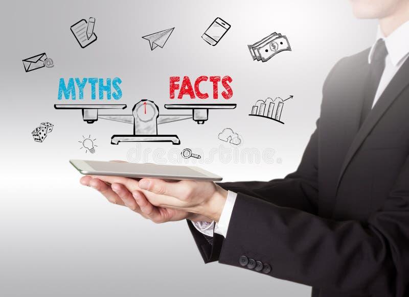 Mythen gegen Tatsachen balancieren, der junge Mann, der einen Tablet-Computer hält lizenzfreie stockfotografie