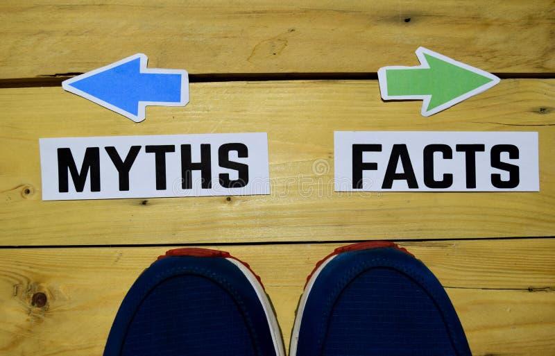 Mythen oder Tatsachen gegenüber von Wegweisern mit Turnschuhen auf hölzernem stockbild