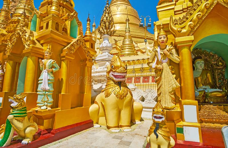 Burmese Nat statues in Shwedagon, Yangon, Myanmar. The mythic animals chinthe leogryphs, nagar serpents and Nat Spirit statues among the shrines with Shwedagon royalty free stock photo