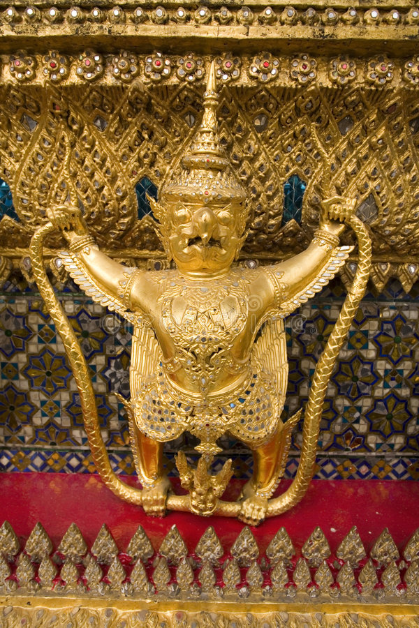 Mythical gold Buddhist statue. Details of a small gold statue of a mythical Buddhist creature, half man and half bird royalty free stock image