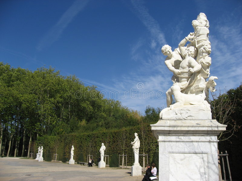 Mythological Statue Versailles Garden. A white mythological statue of Aristaeus and Proteus (Proteus is tied to a rock) and the statues around the Fountain of stock images