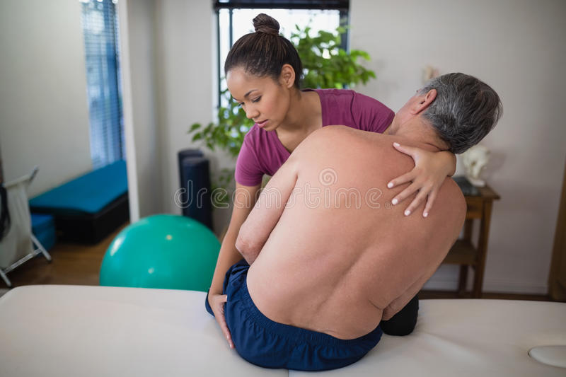 Nádegas de exame do terapeuta fêmea novo do paciente masculino superior descamisado que senta-se na cama fotografia de stock royalty free