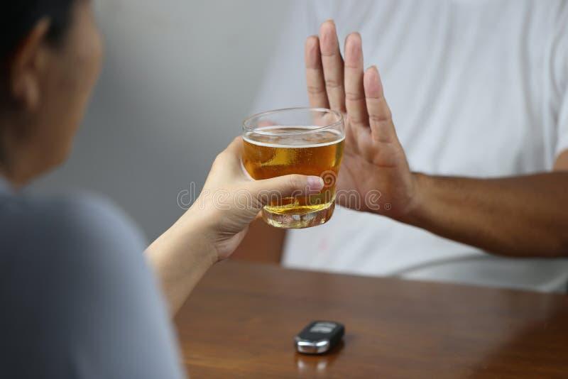 Não beba e não conduza o conceito, mão da jovem mulher que guarda vidros do gesto da parada da cerveja e da exibição do homem e q fotos de stock