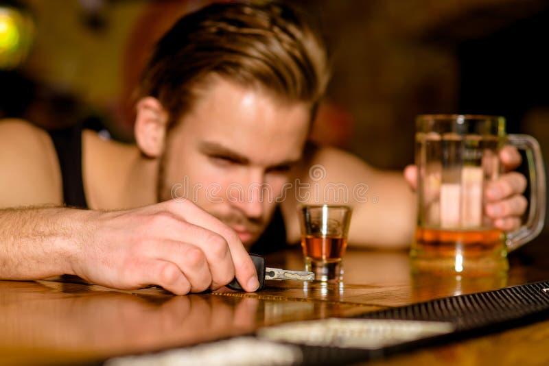 Não conduza bebido Bebedor do homem com chaves do carro no bar Cerveja considerável da bebida do homem no contador da barra Vicia fotografia de stock royalty free