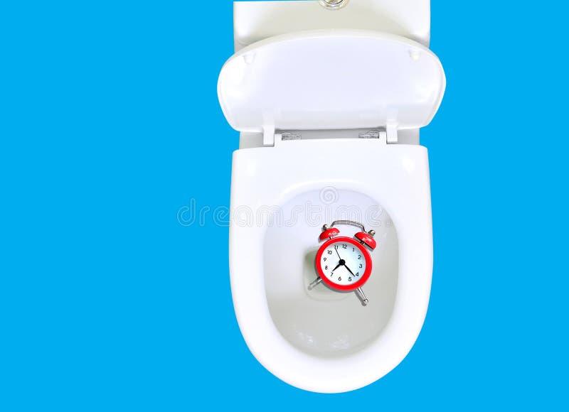 Não desperdice seu conselho do tempo O despertador está na bacia de toalete Desperdi?ando o conceito do tempo Isolado no azul, es imagens de stock royalty free