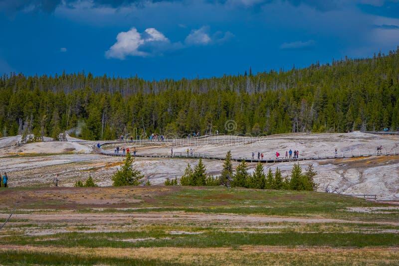 Não identificado peoplewalking a entrada em erupção fiel velha no parque nacional de Yellowstone em um passeio à beira mar cercad fotografia de stock