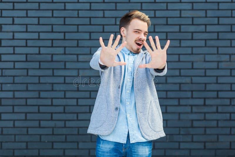 Não, pare por favor Retrato do homem louro novo considerável assustado na posição do estilo ocasional com gesto de mãos receoso d foto de stock royalty free