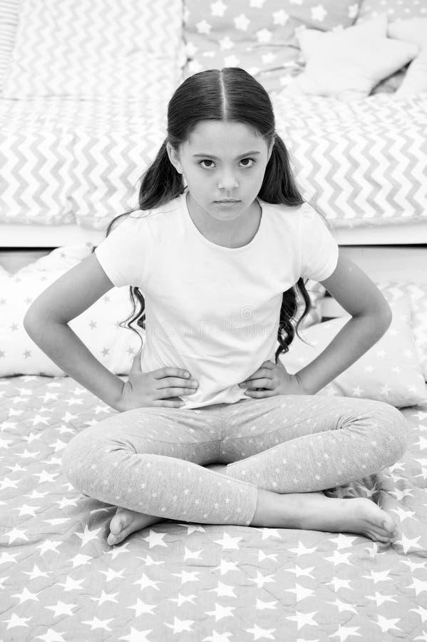 Não perturbe a criança antes do sono A criança da menina senta-se na cama em seu quarto A criança infeliz alguém entrou em seu qu imagem de stock