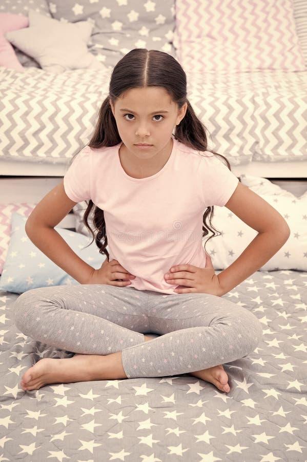 Não perturbe a criança antes do sono A criança da menina senta-se na cama em seu quarto A criança infeliz alguém entrou em seu qu fotografia de stock