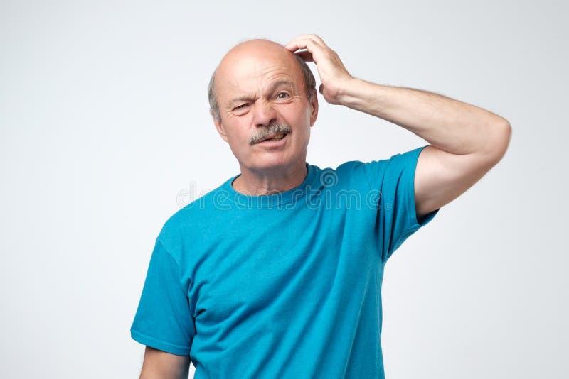 Não sure Adulto maduro no t-shirt azul que tem uma dúvida fotografia de stock royalty free