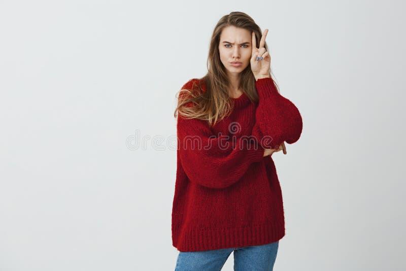Não uma boneca a sorrir toda a hora O estúdio disparou da mulher bonita à moda na camiseta fraca que mostra o sinal de v da vitór fotos de stock