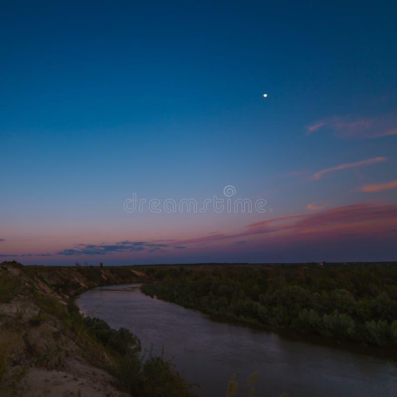 Nächtlicher Himmel mit einem hellen Mond über dem Fluss stockfoto