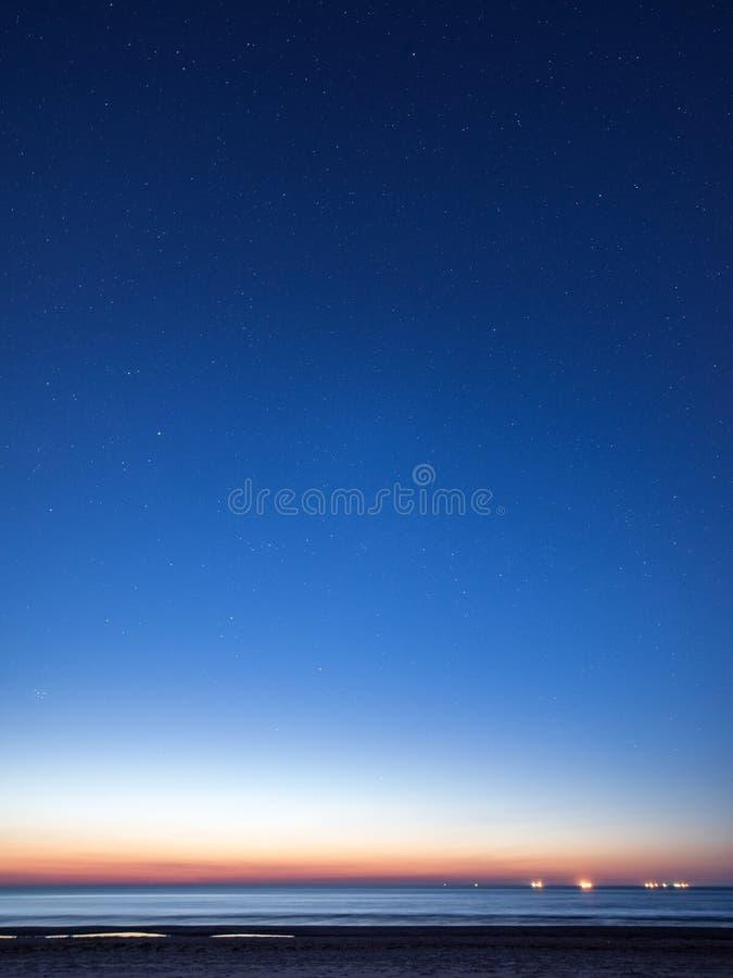Nächtlicher Himmel mit Sternen auf dem Strand Auftragsnummer von Bereichen am Horizont des bedeutenden blauen Planeten stockbild