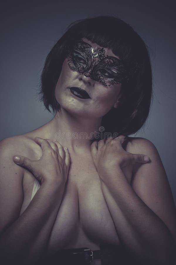 Näck stående av kvinnan med svarta den Venetian maskeringstråden fotografering för bildbyråer