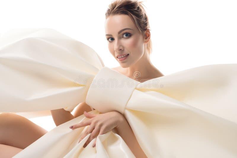Näckt flickasammanträde med den enorma dekorativa pilbågen royaltyfria foton