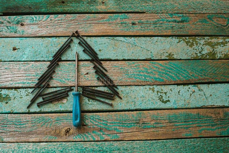 Nägel in Form eines Weihnachtsbaums auf einer Holzoberfläche Das Konzept eines neues Jahr ` s Hintergrundes für das Errichten des stockbild