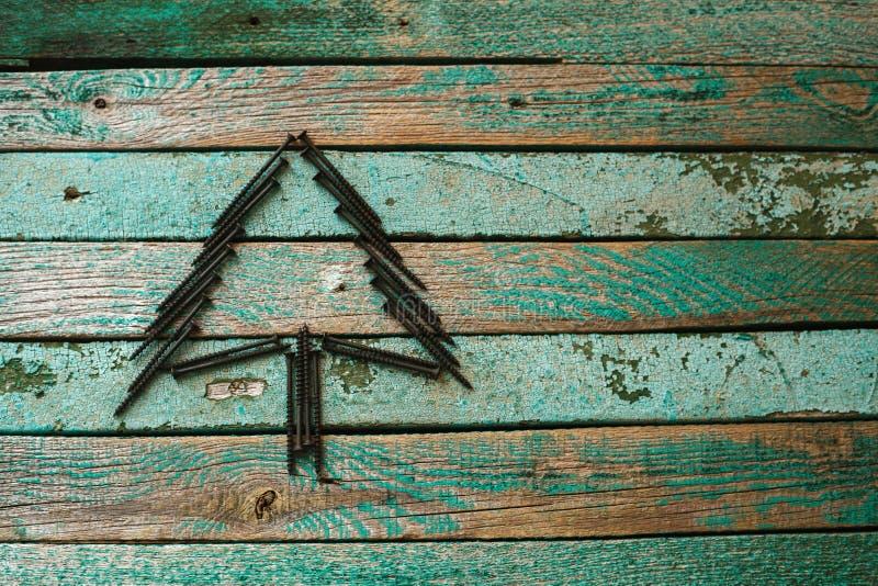 Nägel in Form eines Weihnachtsbaums auf einer Holzoberfläche Das Konzept eines neues Jahr ` s Hintergrundes für das Errichten des stockbilder