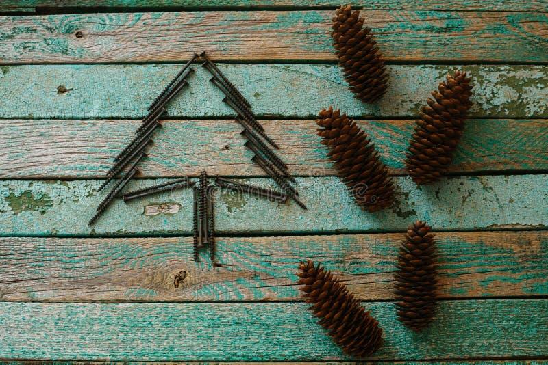 Nägel in Form eines Weihnachtsbaums auf einer Holzoberfläche Das Konzept eines neues Jahr ` s Hintergrundes für das Errichten des lizenzfreie stockfotografie
