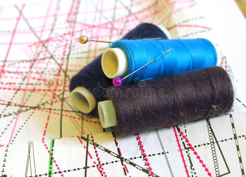 Nähen, nähend auf der Nähmaschine, nähende Versorgungen, farbige Nähgarne, farbige Stücke des Stoffes, Nadeln, Zentimeter stockfotos