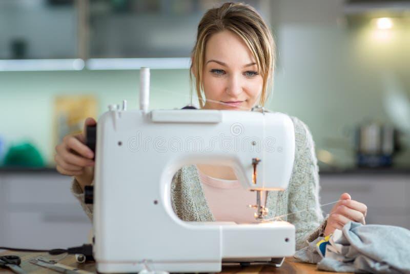 Nähende Kleidung der hübschen, jungen Frau mit Nähmaschine stockbilder