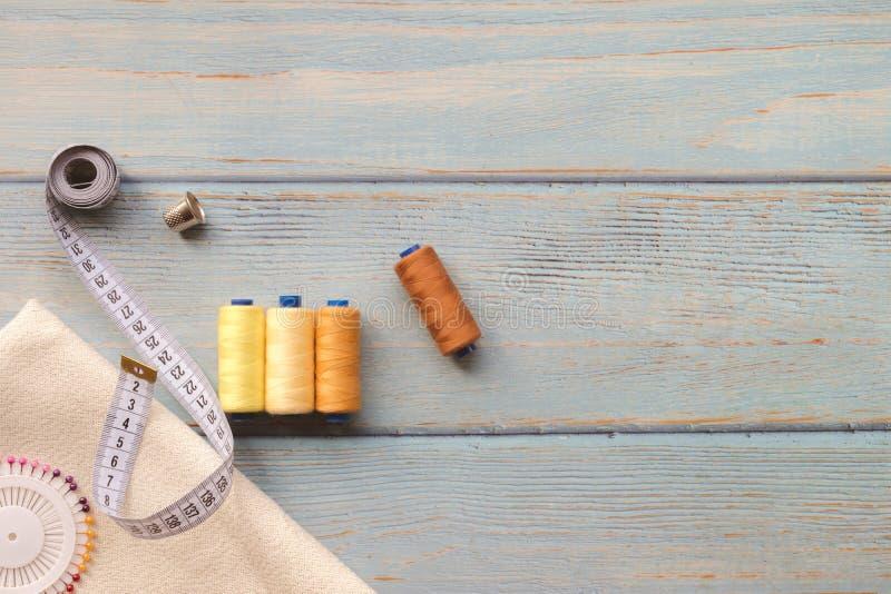 Nähende Zusätze und Gewebe auf einem blauen Hintergrund Gewebe, N?hgarne, Nadel und n?hender Zentimeter Draufsicht, flatlay, stockbilder