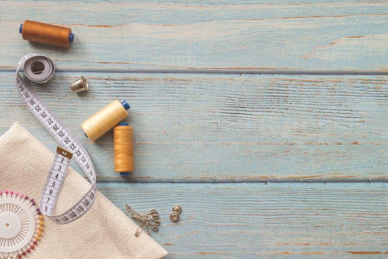 Nähende Zusätze und Gewebe auf einem blauen Hintergrund Gewebe, N?hgarne, Nadel, Kn?pfe und n?hender Zentimeter Draufsicht, lizenzfreies stockbild