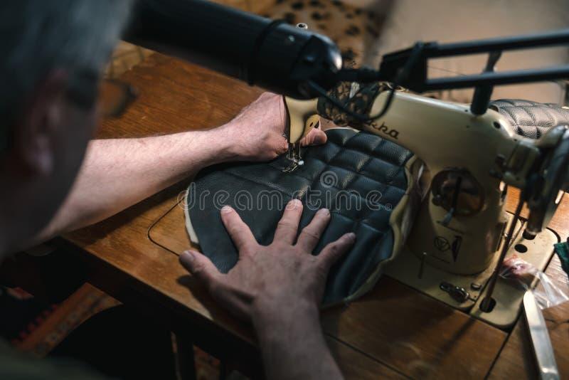Nähender Prozess des Ledergürtels die Hände des alten Mannes hinter dem Nähen Lederne Werkstatt Textilweinlesenähen industriell stockfotos