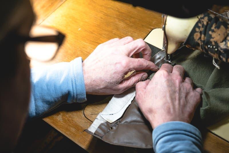 Nähender Prozess des Ledergürtels die Hände des alten Mannes hinter dem Nähen Lederne Werkstatt Textilweinlesenähen industriell stockfoto