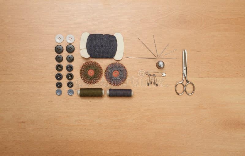 Nähender Satz Scheren, Spulen mit Thread und Nadeln auf hölzernem stockfotos