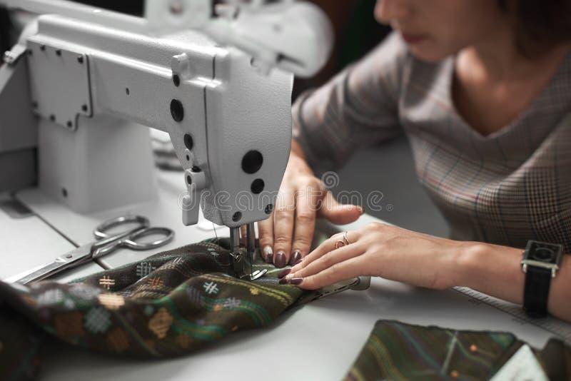 Näherin, die an der modernen elektrischen Nähmaschine in Mode macht exklusives Kleiderstudio arbeitet lizenzfreie stockfotografie
