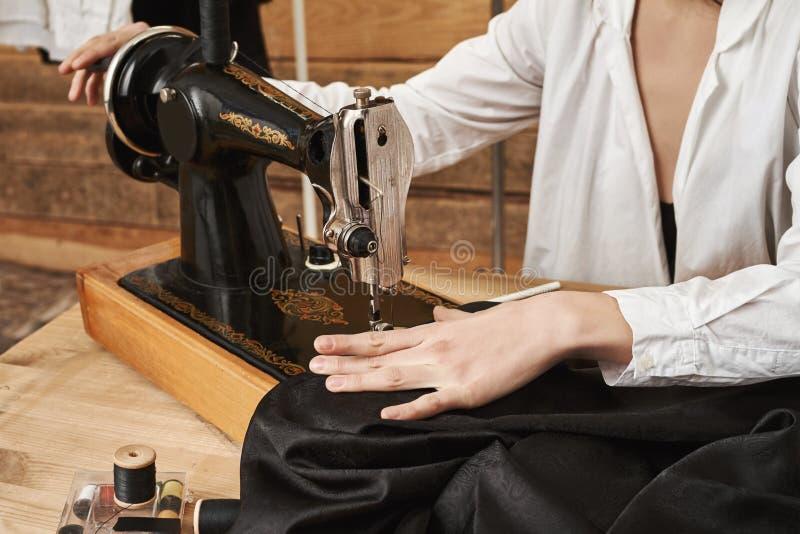 Näherin, die an neuem Projekt arbeitet Weiblicher Abwasserkanal, der mit dem Gewebe, modernes Kleid mit Nähmaschine herein herste lizenzfreie stockfotos