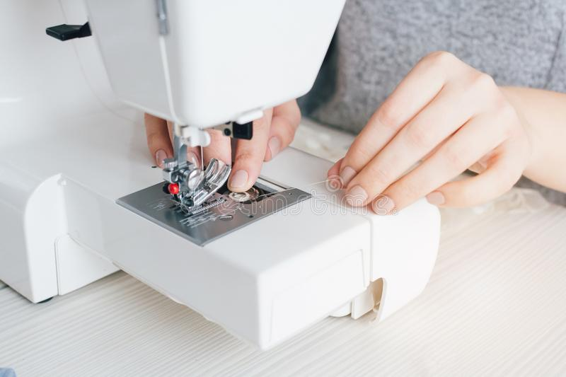 Näherin justiert die Nähmaschine auf Arbeit stockbild