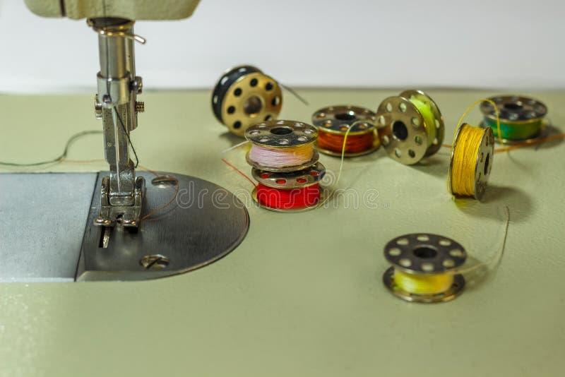 Nähmaschine, auf dem Tisch welcher Lügenspulen mit mehrfarbigen Faden stockbilder