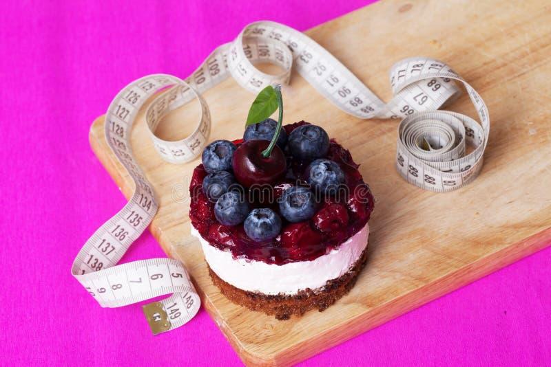 Nähren Sie, Kuchen und Zentimeter, kleine Kuchen, Zahl Schönheitskalorien stockfotos