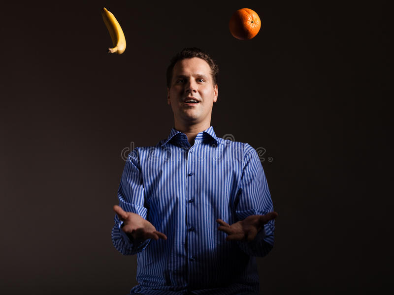 Nähren Sie Nahrung Mann, der mit tropischen Früchten jongliert stockfotografie