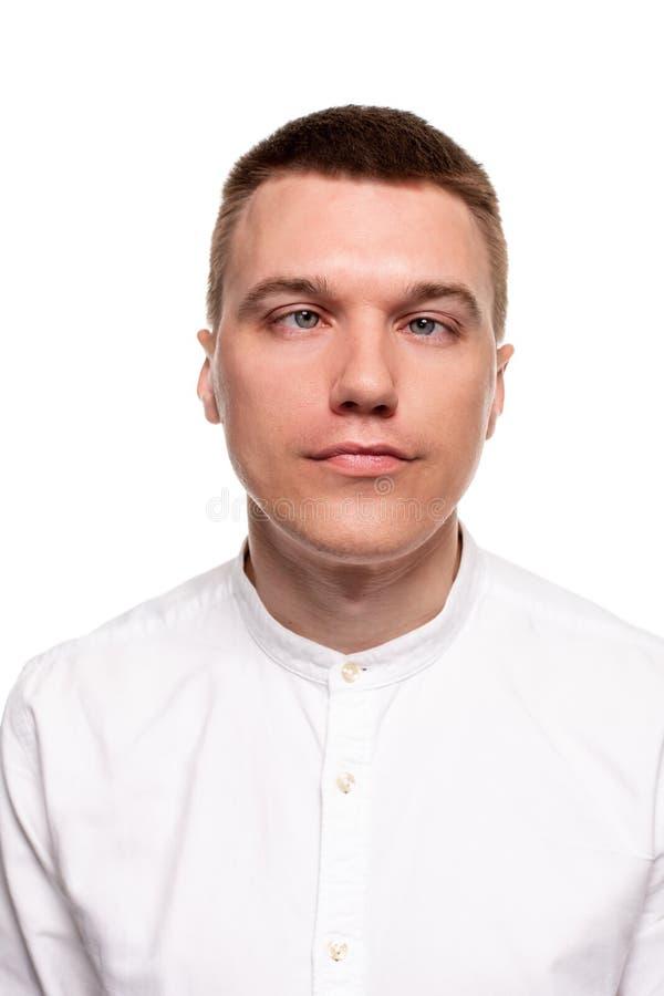 När du charmar den stiliga unga mannen i en vit skjorta gör framsidor, medan stå isolerad på en vit bakgrund arkivfoto