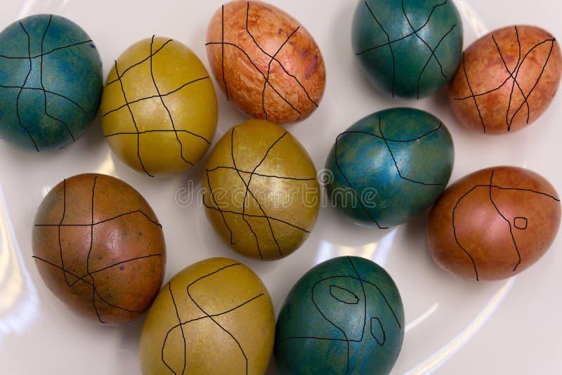 När du färgar ägg för påskferier och att färga med olik färg och tonalitet som använder matcoloranten över, grånar konkret bakgru arkivbild