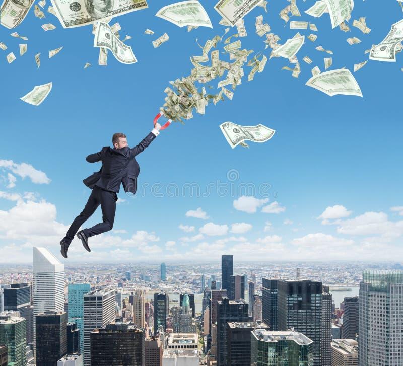 När du flyger den säkra stiliga affärsmannen med magneten tilldrar dollaranmärkningar royaltyfri bild