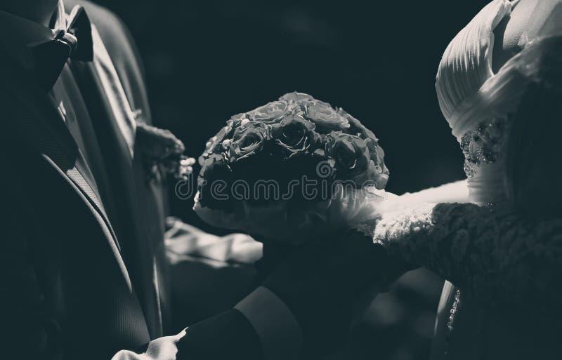 När du gifta sig den eleganta den parbruden och brudgummen som rymmer den härliga buketten, blommar closeupen, svartvit fotoclose fotografering för bildbyråer