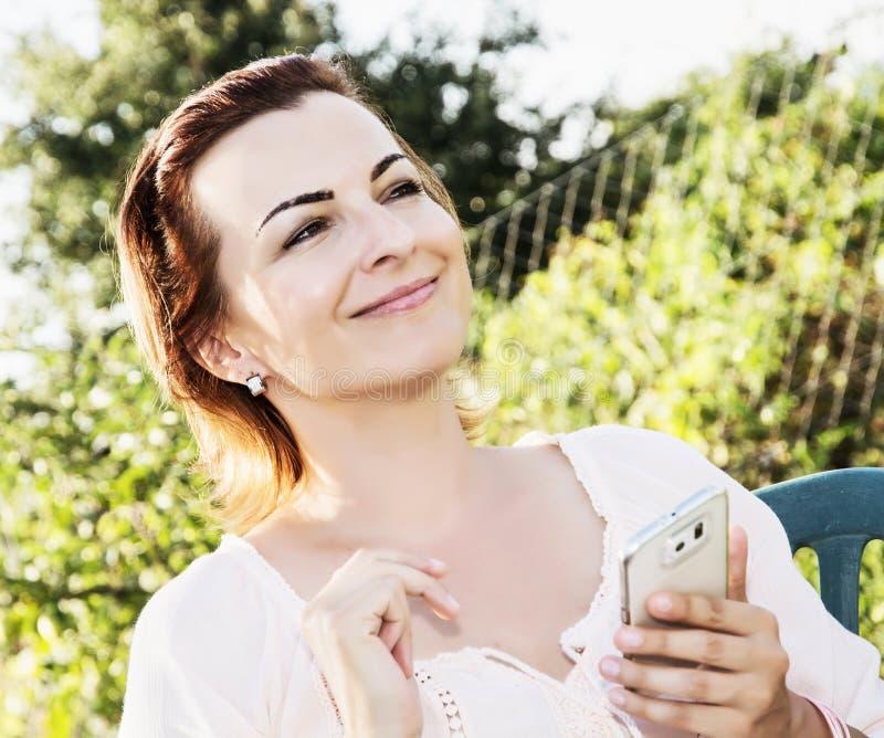 När du ler brunettkvinnan använder den vita smartphonen i utomhus- royaltyfri fotografi