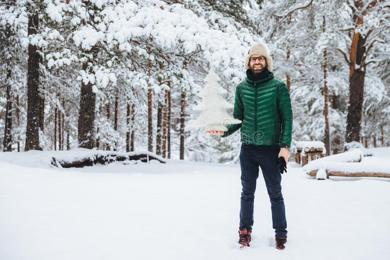 När du ler den glade mitt åldrades manligt med skäggstubb, rymmer det konstgjorda granträdet för den vita vintern, spenderar den  arkivfoton