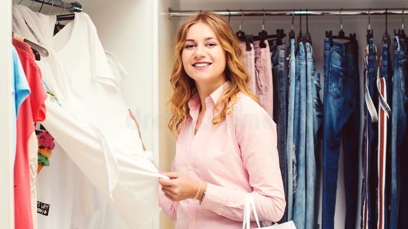 När du ler den härliga flickan gör köp i kläderlager H?nger l?s h?llande shopping f?r kvinnan S?songsbetonade f?rs?ljningar Lycka arkivfoton