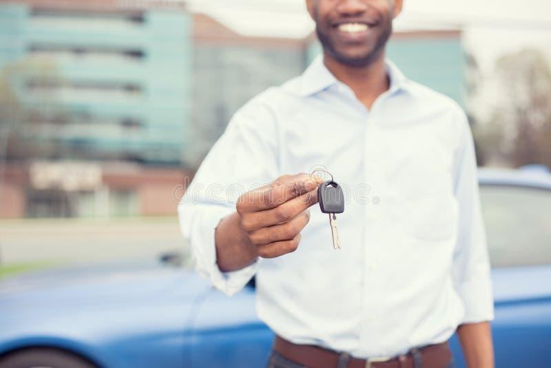 När du ler den hållande bilen för mannen stämmer den erbjudande nya blåa bilen på bakgrund arkivbilder