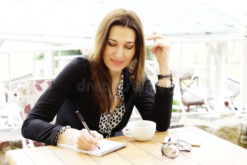 När du ler den lyckliga affärskvinnan gör anmärkningar i en anteckningsbok royaltyfria bilder