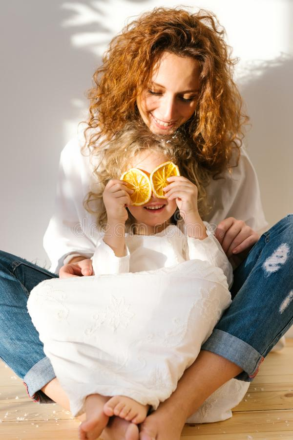 När du ler den lyckliga modern med lockigt hår sitter korsade ben på golv med hennes dotter som har gyckel, och räkningar synar m arkivfoton