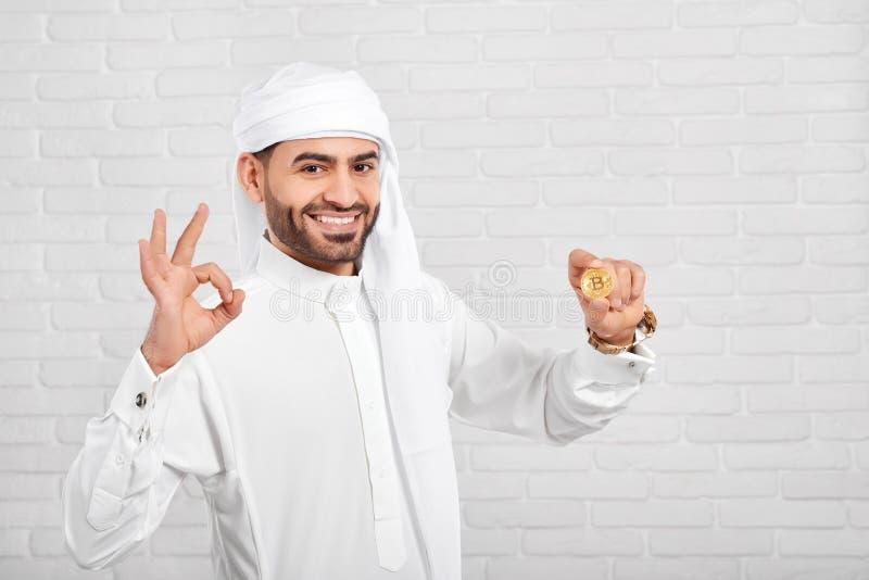 När du ler den muslimska mannen håller bitcoin på den vita bakgrunden royaltyfri bild
